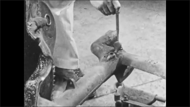 1950s: Close up pan of mower axle, hand inserts rod into joint. Close up, rod inserted into metal joint. Hand removes rod from axle. Hands insert part into mower.