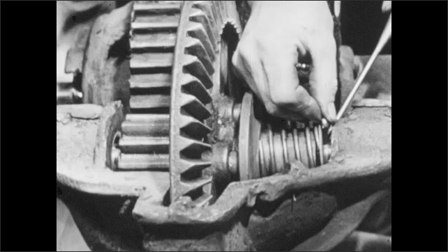 1950s: Close up, hands inserts pin into machine part. Hands insert pins into mower axle. Wrench tightens part on mower.