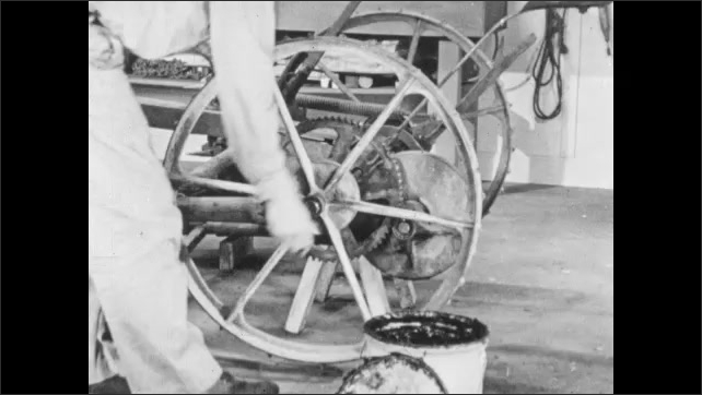 1950s: Man puts wheel on mower axle. Close up, hand locks wheel onto mower.
