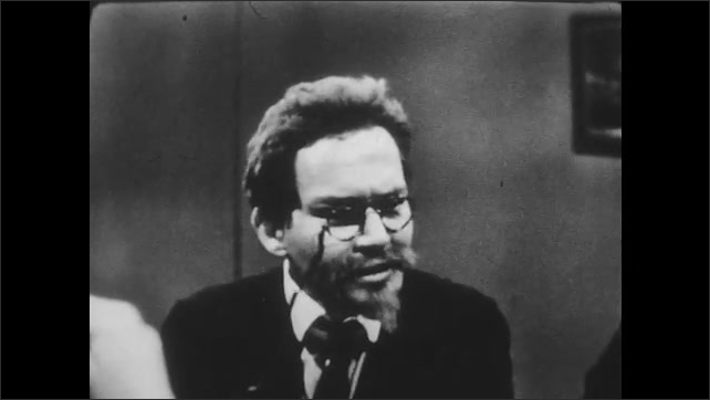 1950s: USSR: man with glasses on string speaks in meeting. Smoke in meeting. Trotsky in meeting. Men discuss politics at table