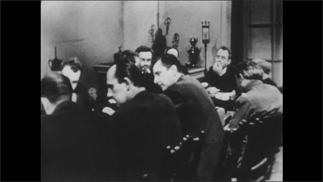 1950s: USSR: executive committee sit at table in meeting. Men sit around table. Secretary stands in meeting. Man reads notes
