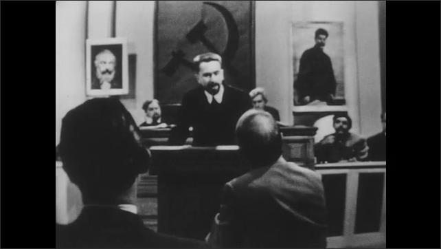 1950s: Meeting.  Man stands at podium and speaks.  Men sit and listen.