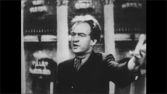 1950s: Man speaks and gestures.  Man smokes.