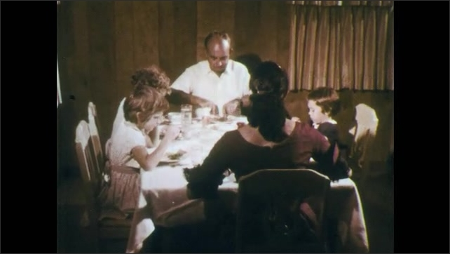 1960s: Can thrown into garbage bag. Woman opens fridge. Empty food containers thrown into garbage bag. Family sits at table, eats. Man shoos away fly, shakes head. Woman eats, shoos away fly.
