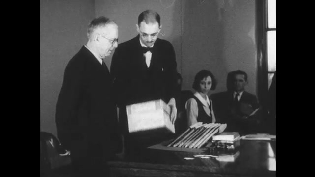 1930s: Group of men sit in room watching man make a presentation. Presenter shapes a box, takes an item out of the box and places it on the table.