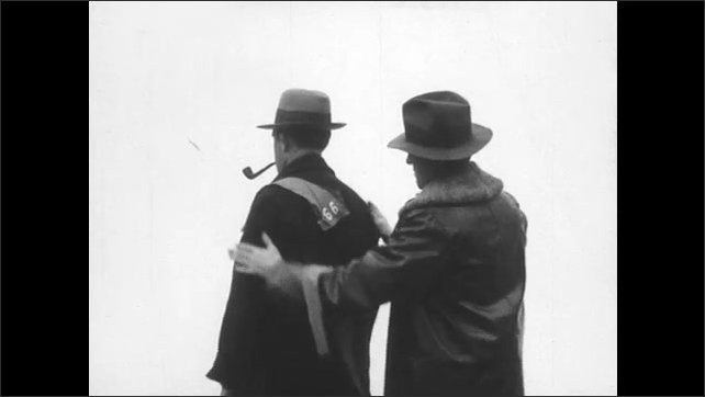 1930s: man pins warning cloth with number on hunter with pipe's coat and wraps sheet around hat.