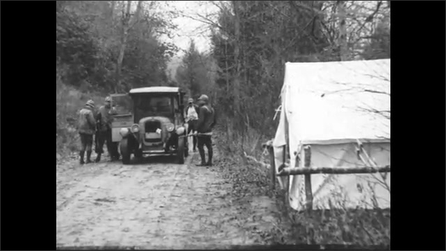 1930s: men with rifles and hats step off truck on dirt road and walk to tent in woods.