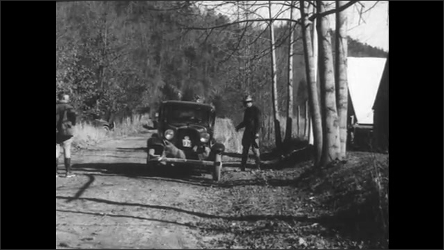 1930s: man shakes hands with park ranger, gets in car and drives down dirt road with dead deer attached to bumper.