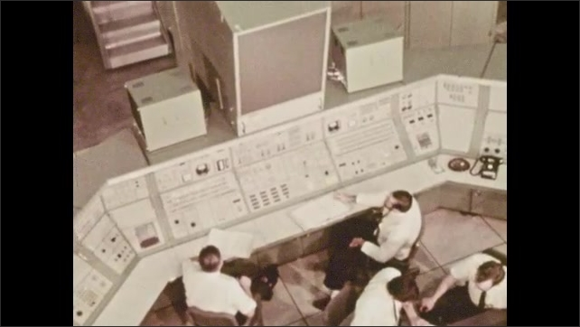 1970s: men at control panels and command center work with the astronauts in the lunar lander module during the simulation