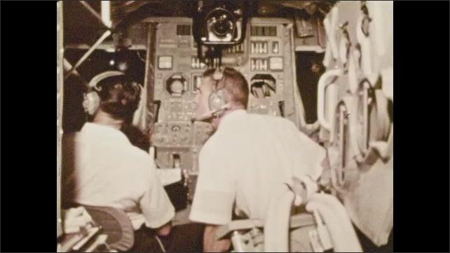 1970s: two astronauts sitting inside the lunar lander module learning how it works, model lunar surface outside of the module's window