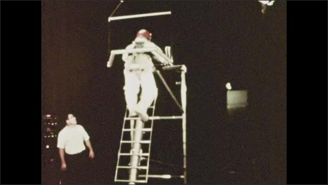 1970s: astronaut wearing harness to experience zero gravity conditions, astronaut wearing a harness sideways and kicking off a wall to experience zero gravity conditions