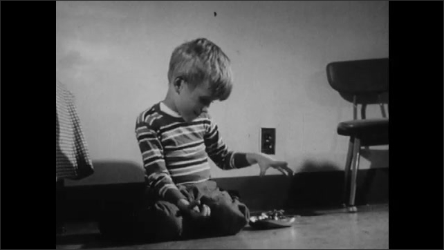 1960s: Boy cries and violently hits himself. Another boy plays with metal dish and rocks back and forth while sucking on rubber stick.
