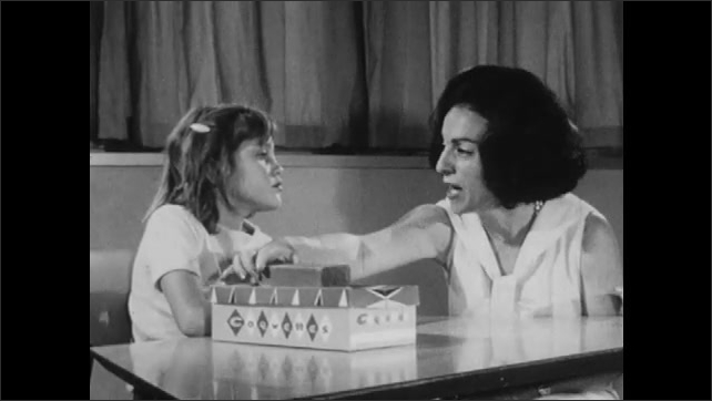1960s: Doctor spanks and yells at girl. Woman asks girl what color the crayon is. Woman asks girl to move block.