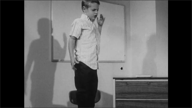 1960s: Boy stands on chair. Woman asks boy questions.