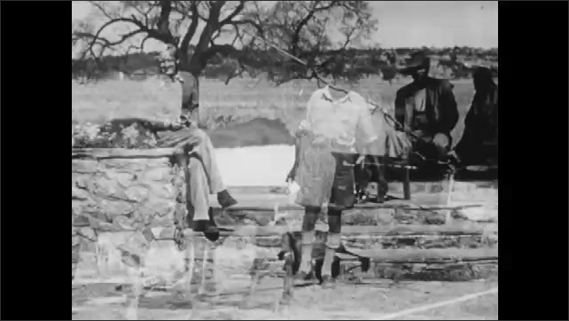 1950s: Man hands check to man. Man hands check to another man. Two people ride in cattle driven cart.