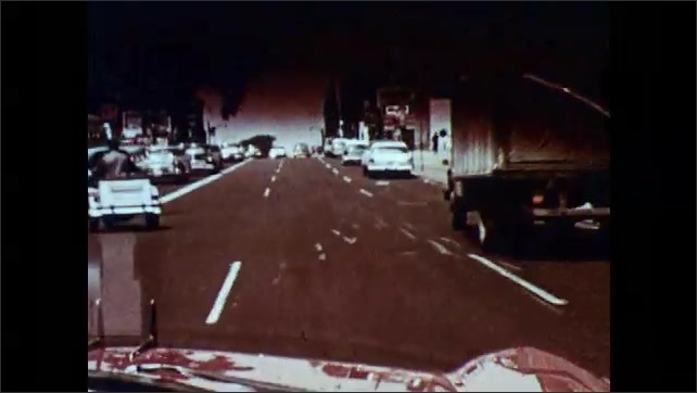 1950s: Ambulance drives down street.