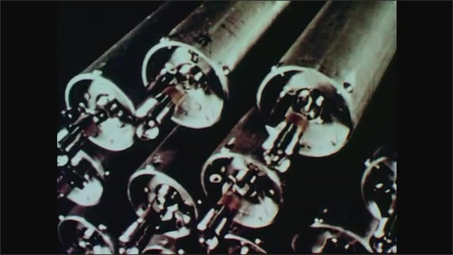1960s: Man inserts specially designed grenades into head of rocket. Two men place head of rocket onto body of rocket.
