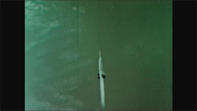 1960s: Rocket launches into sky from pad in desert.