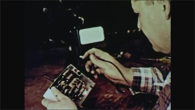 1960s: Man holds and tests electronic device in hand. Man holding device in hands.