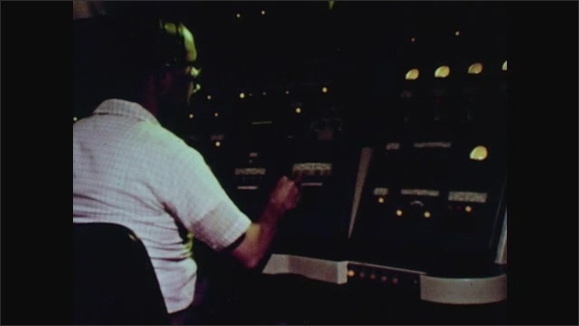 1960s: Radar dish points up at sky. Man at radar controls. Numbers on control change.