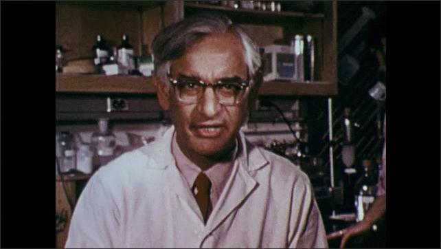 1970s: UNITED STATES: scientist talks to camera. Genes on diagram. Scientific equation on board. Gene splicing research