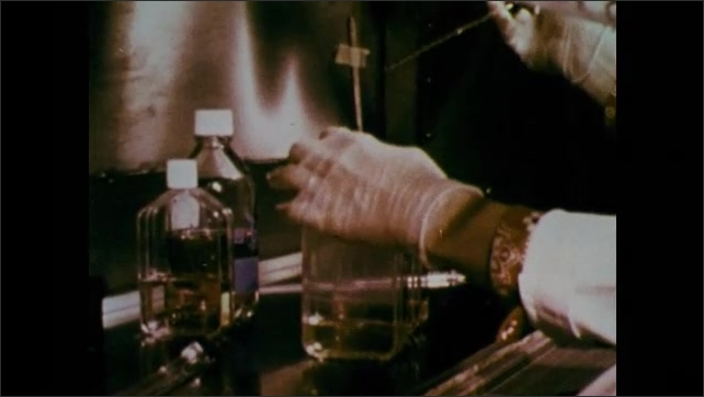 1970s: UNITED STATES: lady works in medical lab. Hands fill bottles with liquid. Puzzle pieces animation