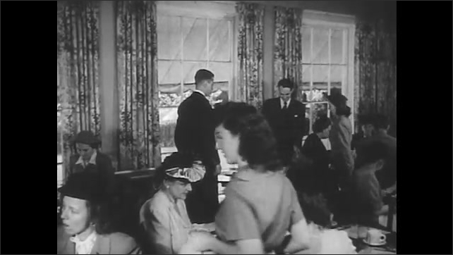1940s: Manager leads couple to restaurant table. Manager pulls out chair for woman and hands menu to couple.