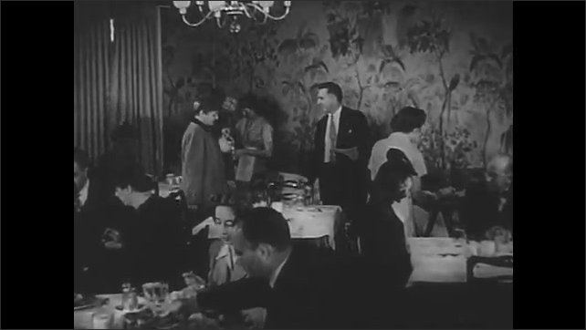 1940s: Manager leads customers into busy restaurant dining room. Manager seats customers at table and gives menus.