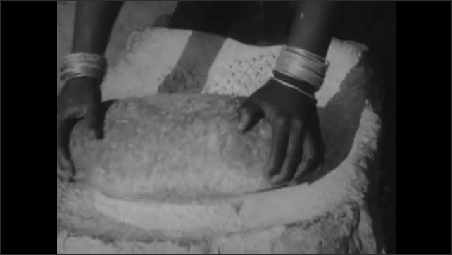 1940s: Two women roll stones over beds of corn, crushing into meal, with child in between. Child watches women. Men sit in circle around leader, doing work.