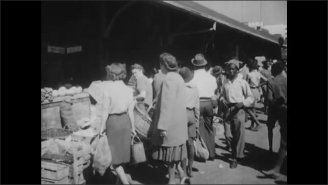 1940s: Man, woman, boy and girl stand on sidewalk in city, talking. Woman and girl walk one direction, boy and man walk other. Woman and girl at produce stand. Fruit in bins.