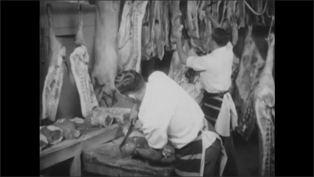 1940s: Woman and girl walk up to counter at butcher shop. Man cuts meat in butcher shop.