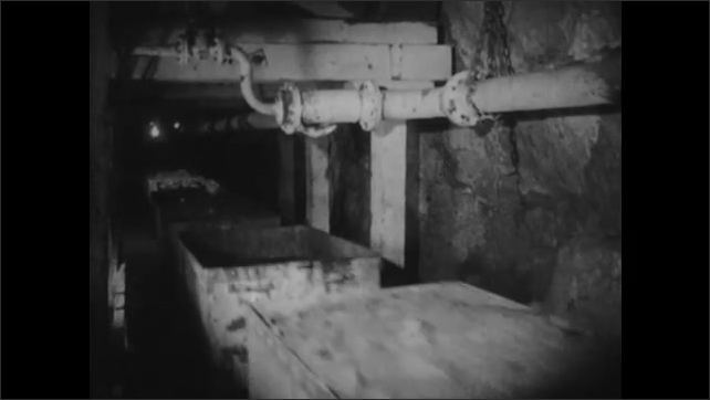 1940s: Riding in cart down tracks in mine. Man rides in cart down tracks in mine. Cart enters platform which turns cart over dumping debris from cart.
