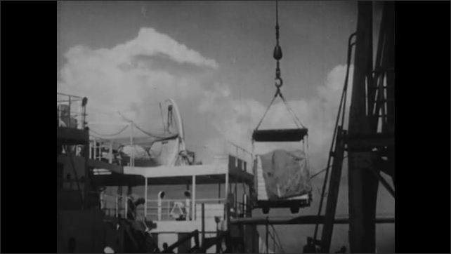 1940s: Crane lifts cargo onto docked ship in harbor of town. Crane loads boxes onto ship.