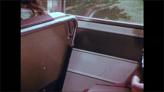1970s: Girl picks up trash on school bus.  Scratches on bus interior.  Girls and boys ride bus and talk.