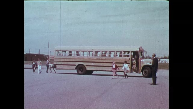 1970s: Teacher stands at front of classroom and speaks.  Students perform bus evacuation drill.  Feet on bus steps.