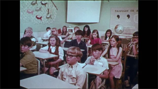 1970s: Girl raises hand and speaks.  Children with umbrellas walk to house.  Teacher speaks to class.  Class sits and listens.  Students get onto school buses.