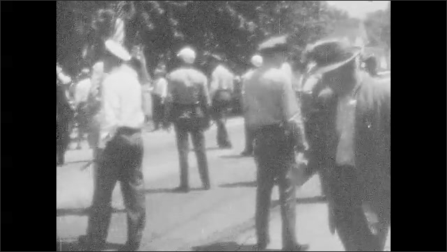 1950s: UNITED STATES: police arrest man at protest. Police escort man to car. Fire crew spray protestors with hoses.