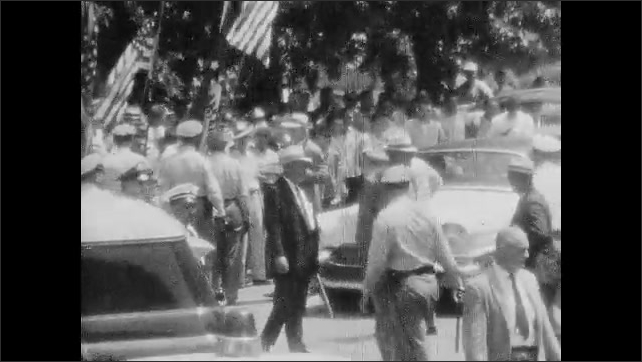 1950s: UNITED STATES: police man slams door on car. People take part in rally. Police protect area. Police arrest man.