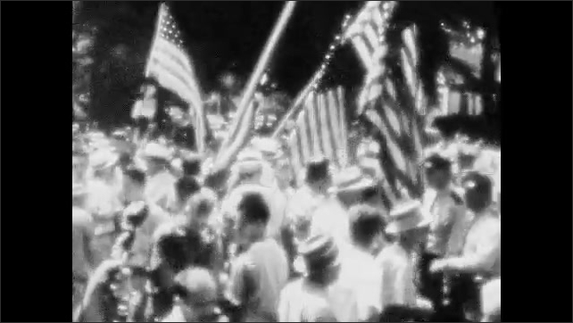 1950s: UNITED STATES: crowd gather to listen to speaker. Police move protestors along. Protestors carry flags