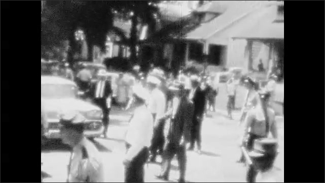 1950s: UNITED STATES: crowd gathers in street. Car drives along road through crowd.