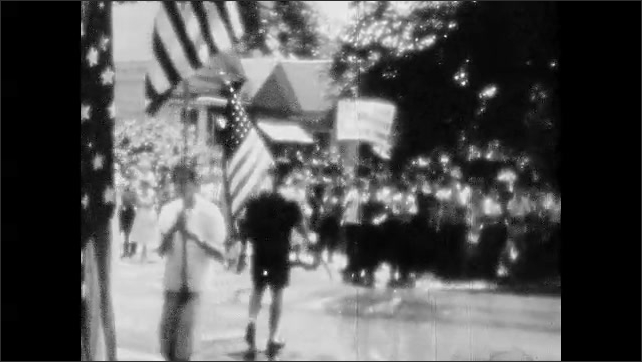 1950s: UNITED STATES: young people stand under tree at protest. Men carry American flags at protest. People march along road.