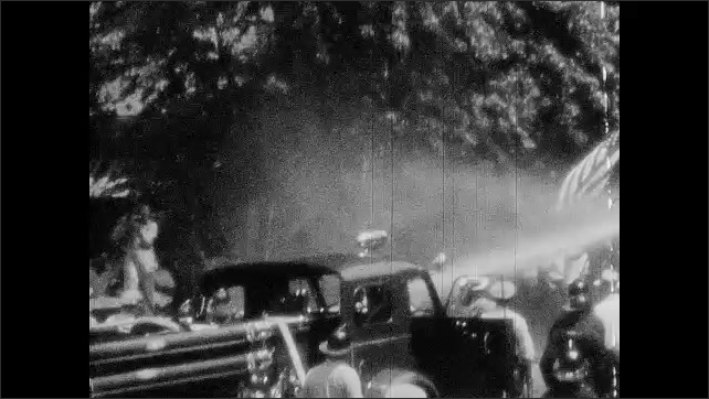1950s: Police arrest men and load them into squad car.  Firemen shoot water down street.