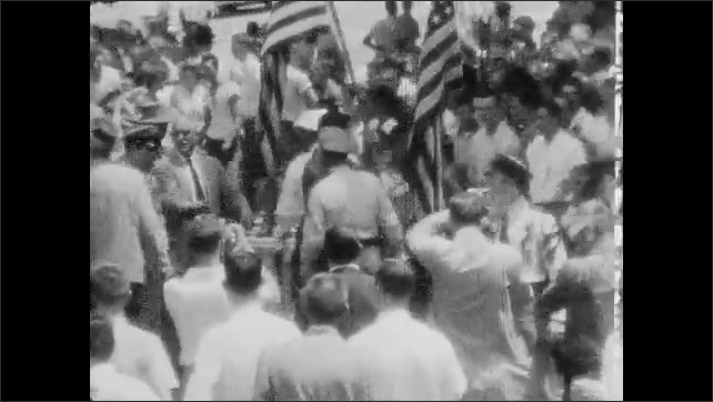 1950s: Men stand together and talk.  Crowd of protesters.  People march down street.  Policeman walks with arrested man.