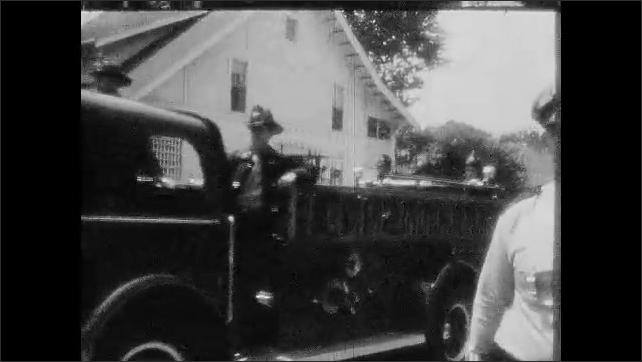 1950s: Policemen stand in front of crowd of protesters.  Fire truck drives down street.  Police arrest man.  Firefighters prepare to use hydrant.