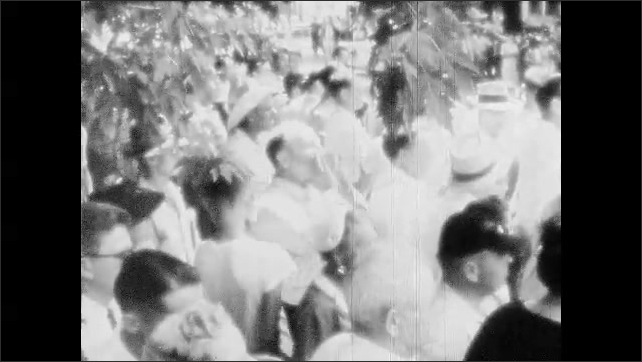 1950s: Unruly crowd.  Man yells.  Police force suspect into back of police car.