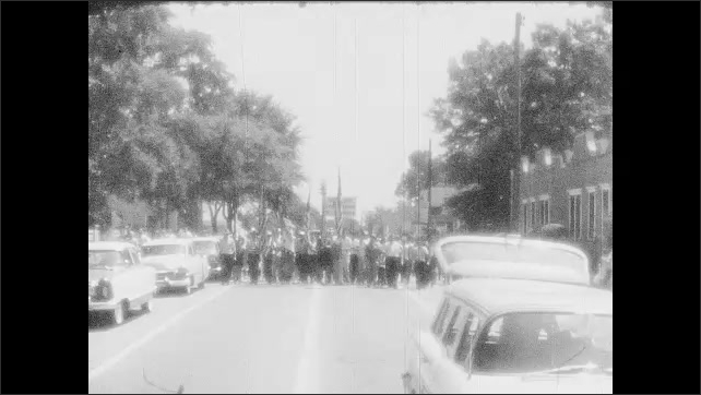 1950s: Car passes.  Policemen wait in street.  Protest march.
