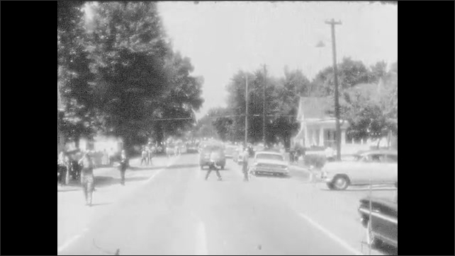 1950s: Cars drive down street.  Protest march.