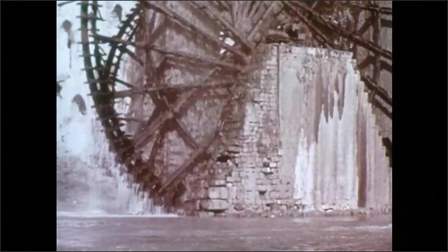1950s: Horse mill, horse walks in circles, wheel turns, man sweeps grain. Hand turns pages of handwritten book in Arabic, diagrams of gears. Water wheel spins in river.