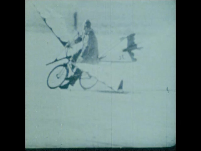 1970s: Hopping helicopter car. Man is pushed on a bicycle with wings until it begins burning. Helpers get him off the bike and put out his own fire.