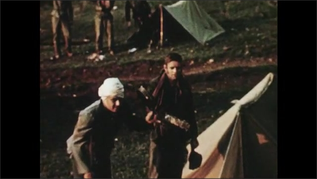 1950s: Close up, man stands up. Man stands up. High angle tracking shot, soldiers saluting. Close up of fire.